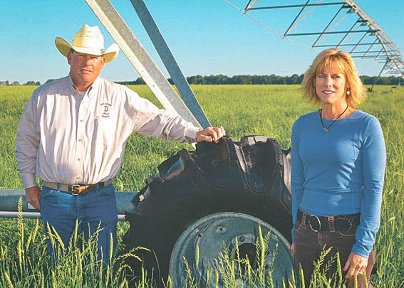 husband and wife standing in a field by irrigation rig