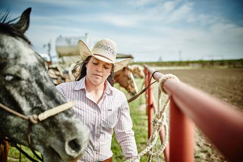 Young woman farmer on cattle ranch land with a horse.