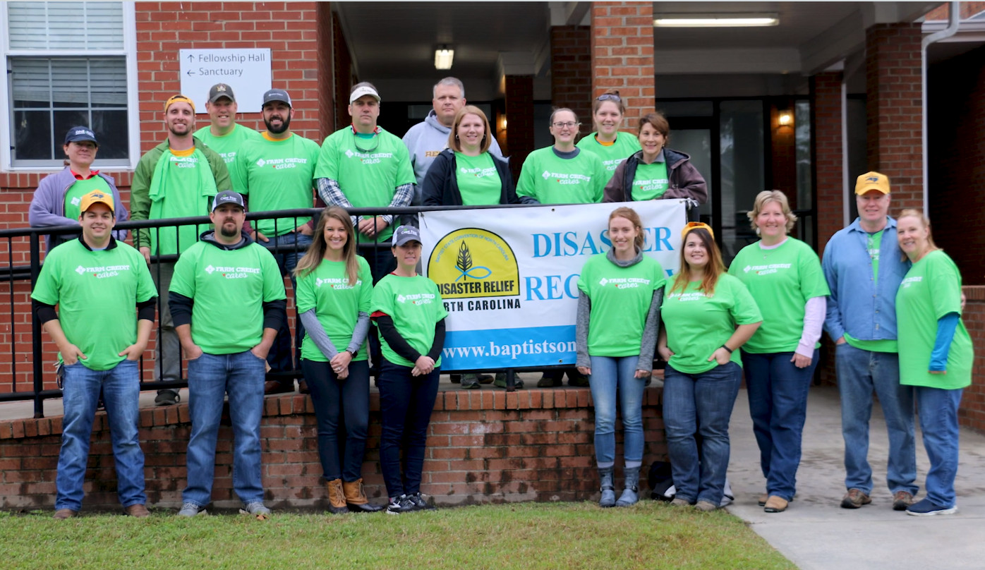 Farm Credit staff stand together in front of a church wearing matching lime green t-shirts ready to volunteer for hurricane relief.