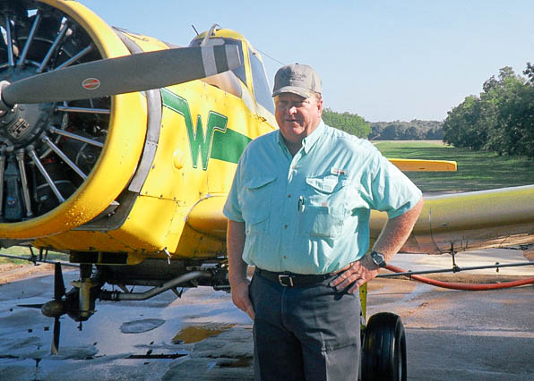 man in a blue shirt standing beside a plane