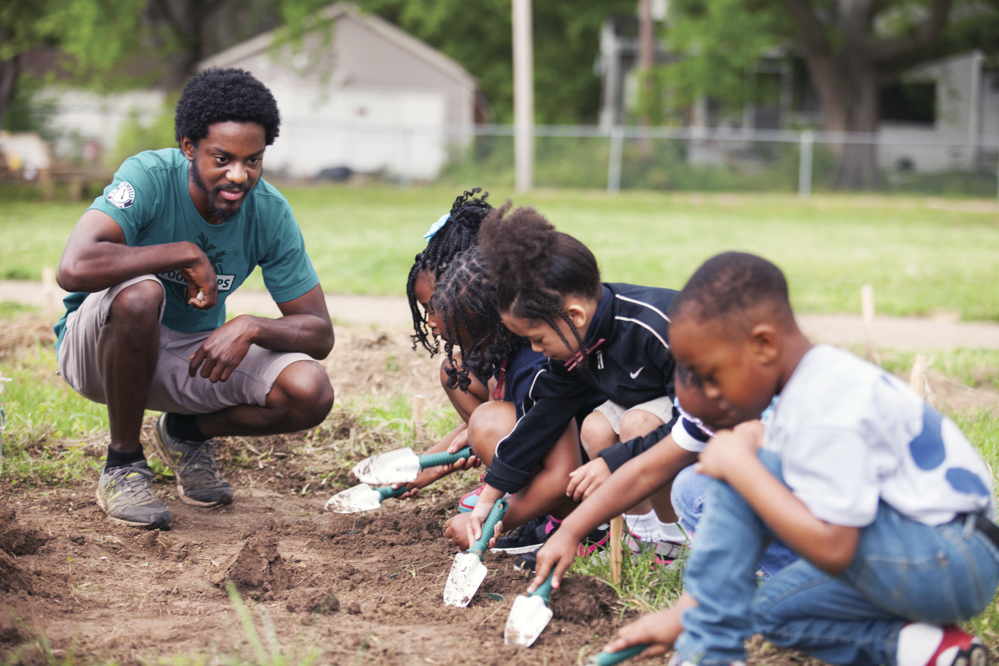 A FoodCorps service member teaches young kids in the garden.