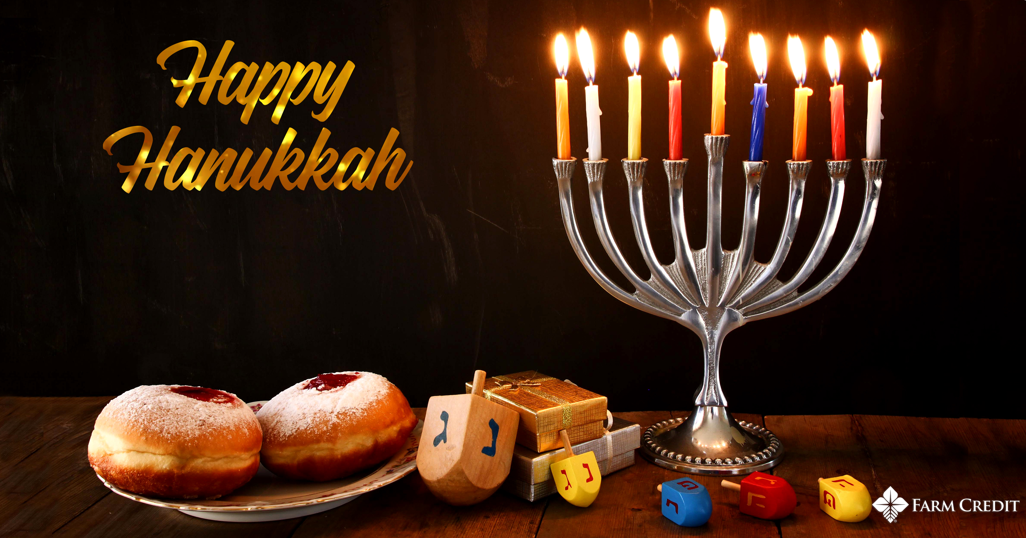 hanukka text on screen graphic with menorah lit and dreidals