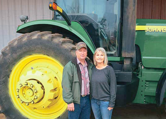 husband and wife standing in front of a tractor